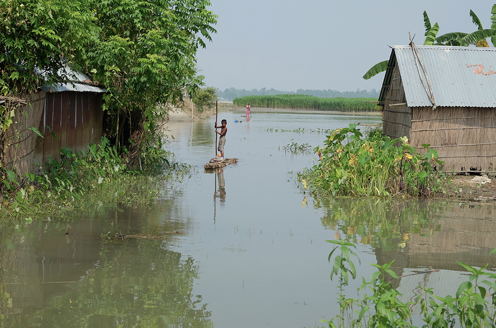 A boy moves through a flooded area of his village in Bangladesh.