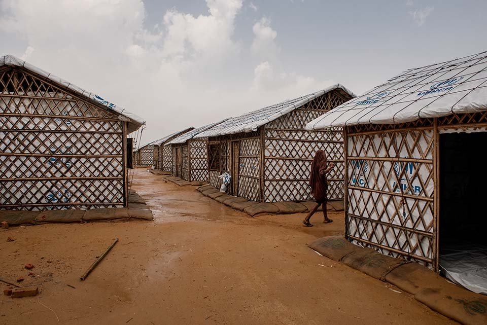 a woman walks among Rohingya camp shelters in Bangladesh
