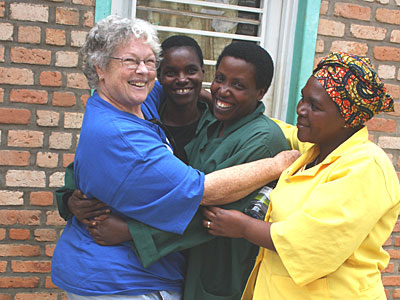 Sandra Basgall, left, a CRS advisor on monitoring and evaluation for Central Africa, hugs several partners, including a social worker and community health workers, in Rwanda. Photo by Kevin Kostic/CRS