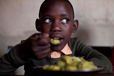 Emerance Niwegisubizo, 12, eats some of the vegetables her family grew in Rwanda with help from CRS, Caritas and Keurig Green Mountain. Photo by Laura Elizabeth Pohl for CRS.