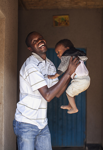 Deodate Nsengimana plays with daughter Olga at their home in Rwanda. Photo by Laura Elizabeth Pohl for CRS