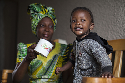 Odette Mukamurenzi, with daughter Olga, participates in a CRS program that teaches families how to grow and prepare nutritious food, and save money. Photo by Laura Elizabeth Pohl for CRS