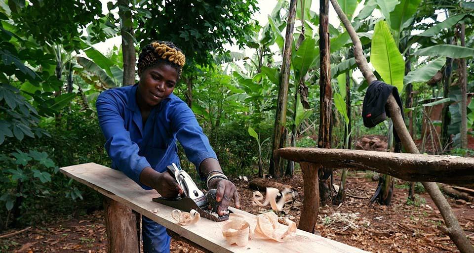 Rwandan uses a hand plan to true a board