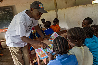 Sannah Turay teaches first and second graders in his class at a CRS-supported school in Sierra Leone. Photo by Karen Kasmauski for CRS