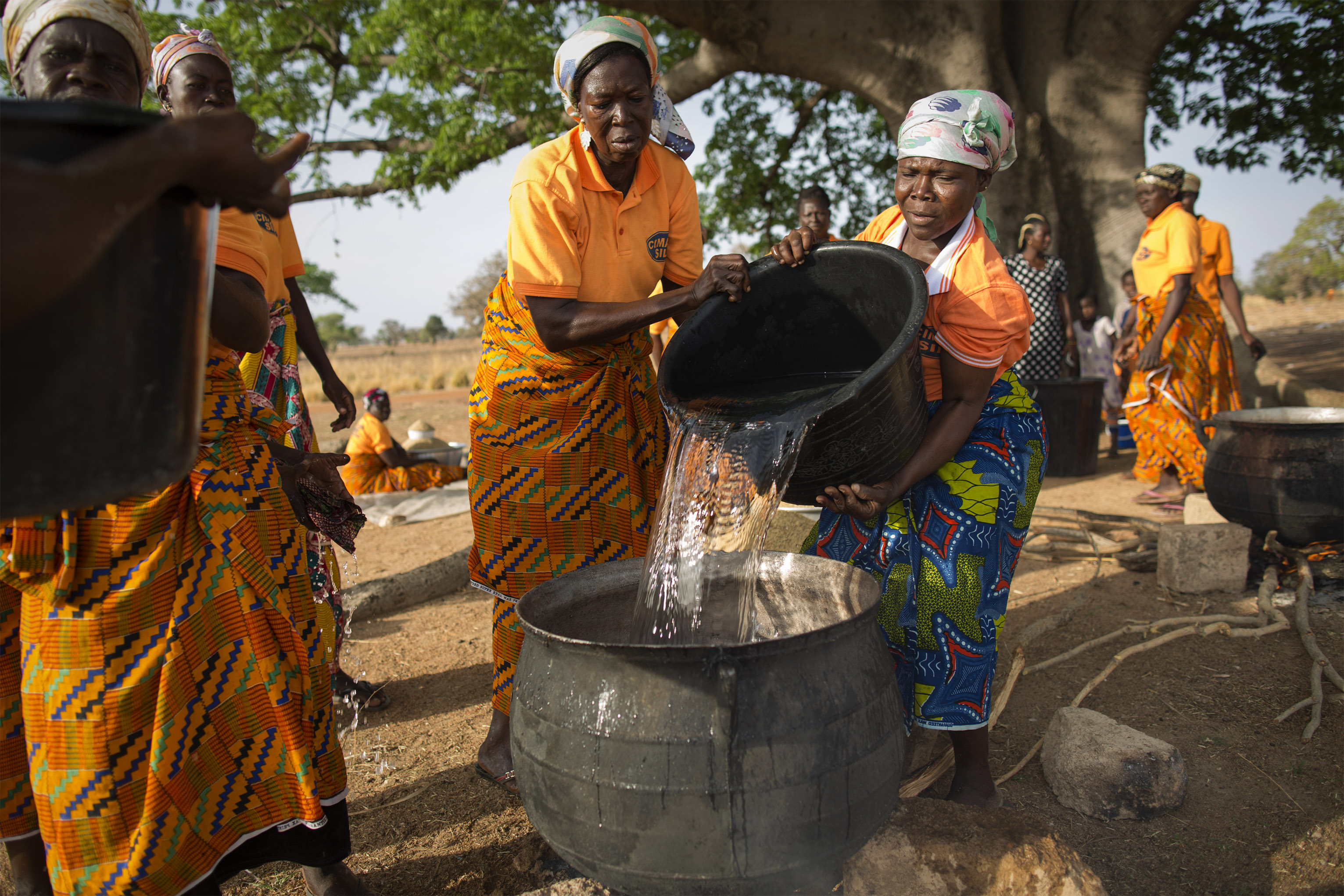 When rising temperatures bring destructive weather patterns and cause crops to wither, the women in Awaradoni village work together as a support system. Here, they are processing and making rice. Photo by Jake Lyell for CRS
