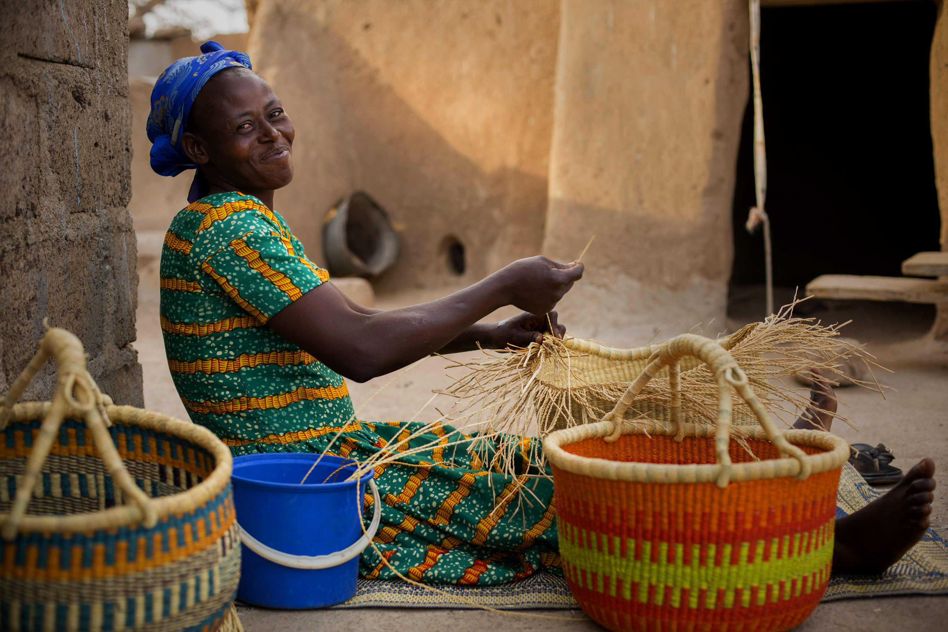 But thanks to a savings program, Nyaamah has a new dream: weaving straw baskets to sell to support her family. Photo by Jake Lyell for CRS
