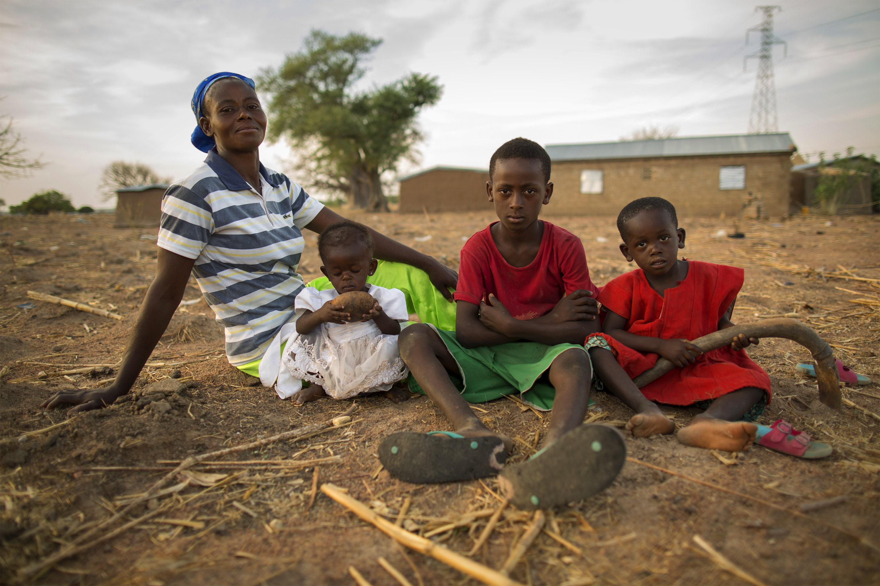 Nyaamah sits with her children Nma, Prince and Edmond on their sometimes profitable farmland. Photo by Jake Lyell for CRS