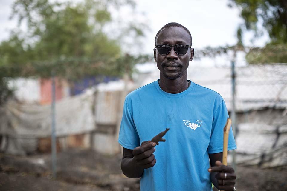 South Sudanese man in sunglasses facing camera and holding clay gun