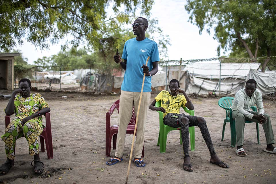 South Sudanese man speaking to a group of men