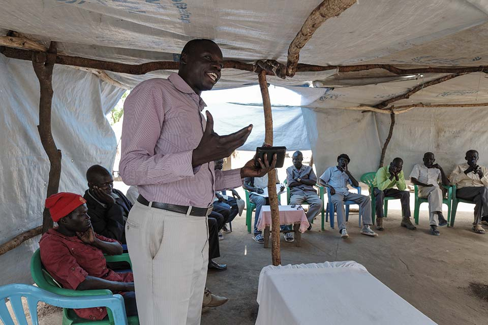 South Sudanese assistant pastor speaks to a gathering in Uganda