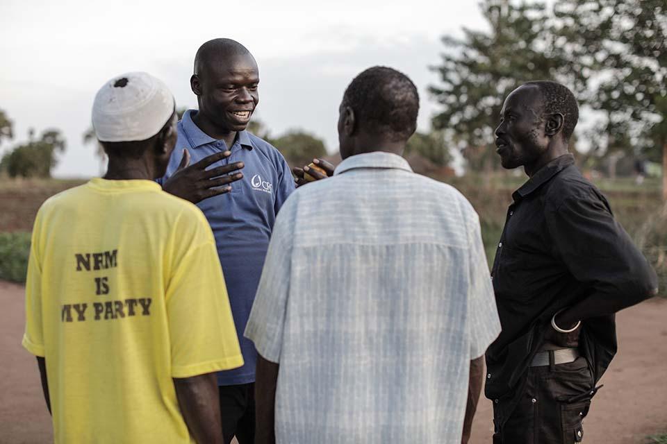 South Sudanese refugee talking with 3 men in Uganda