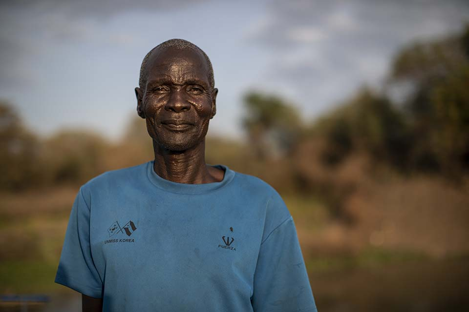 South Sudanese vegetable farmer tands in a field prepared for use