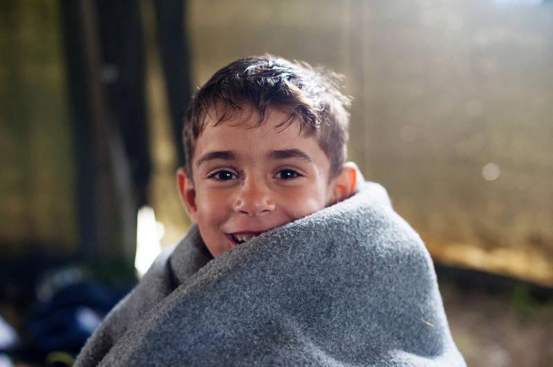 Muhamed, 5, inside a tent at a refugee aid point in Kanjiza, Serbia, before traveling to Germany with his father. CRS is providing basic medical services and information at the aid station.
