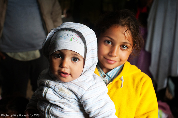 Syrian refugee Obama Basheer, holds her sister, Joud, inside a refugee aid station in the Kanjiza, Serbia. Syrian refugees arrived by double-decker bus from Belgrade, CRS is assisting the Syrian people in transit all through the region.