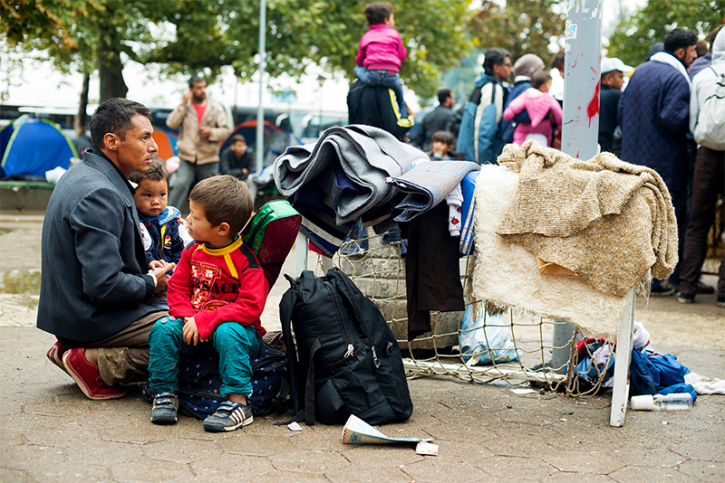 Refugee families wait for transportation to the Hungary border at a park in Belgrade, Serbia. Photo by Kira Horvath for CRS