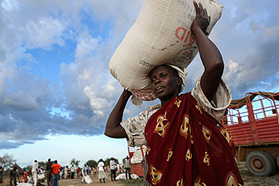 A woman in Makol Cuei, South Sudan, balances a 110-pound bag of sorghum she received as payment for 20 days of road construction. Photo by Sara A. Fajardo/CRS