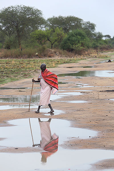 A woman walks along a finished road outside of the village of Makol Cuei in South Sudan. Roads provide access to markets and other villages, and offer safety from attackers. Photo by Sara A. Fajardo/CRS