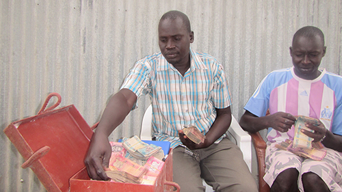James Malueth, left, and John Agau Majok count money in the Maet-de-Ngath Savings and Internal Lending Community's cash box in Jonglei State, South Sudan. Loans from the SILC helped members escape conflict and return to rebuild. Photo by John Gai/CRS