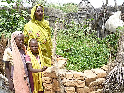 In Sudan, Khadija Musa and two of her nine children stand next to the family's keyhole garden, which provides food for the family plus surplus produce to sell at market. Photo by Mohamed Suliman Ibrahim/CRS