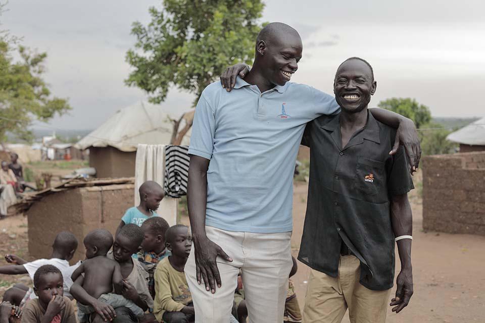 South Sudanese man with arm around his Uganda host friend