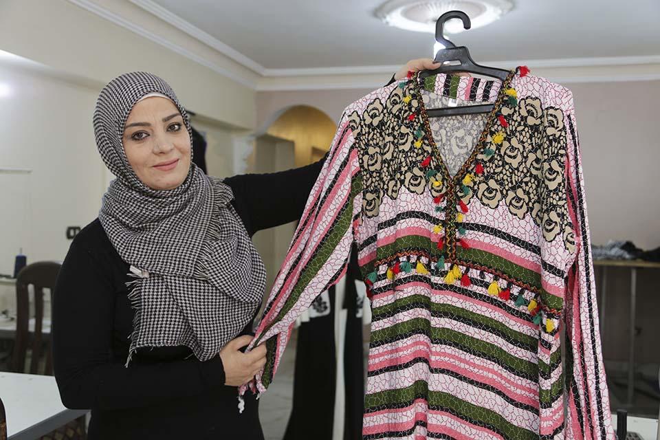 Syrian refugee business woman displays samples of her products