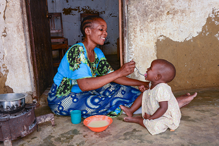 Tatu Omari feeds her daughter Mwanaisha. Tatu and her twin daughters participate in the CRS THRIVE project, which encourages good nutrition and positive parenting. Photo by Philip Laubner/CRS