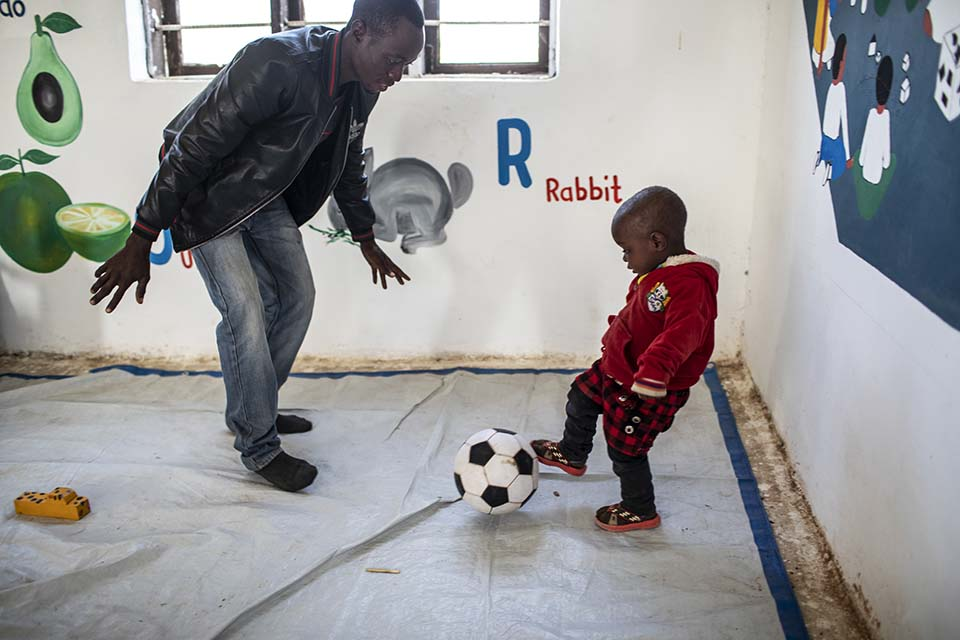 Tanzanian father plays ball with his son