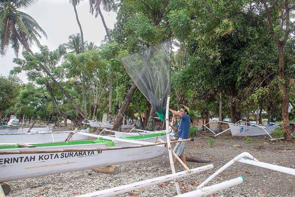 tsunami survivor works fishing net