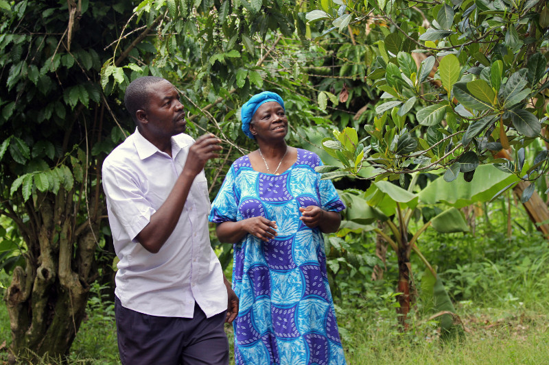 Kabwangu Musar, left, who studied with Farmer-to-Farmer volunteer Velma Gwishiri, right, shows a jack fruit tree on the grounds of a fellow student's home. Mr. Musar studied corporate management and leadership with Ms. Gwishiri. Ric Francis for CRS