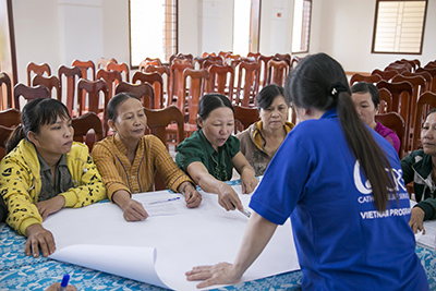 Thien Thi Phan, a farmer from central Vietnam, leads a community discussion about clean water at a CRS training. After the training, Thien will share the information she learned with neighbors who couldn't attend. Photo by Jennifer Hardy/CRS
