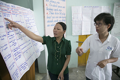 Thien Thi Phan and Duong Thi Bach Nguyen, a CRS project officer, review a disaster preparedness plan. They worked with local government to establish evacuation sites, vulnerable households and fortify early warning systems. Photo by Jennifer Hardy/CRS