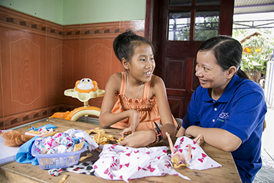 Nguyet shares her latest fashion designs with a CRS staff member during a home visit. Photo by Jennifer Hardy/CRS