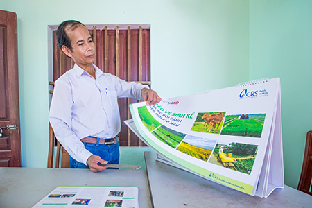 TSG member Vo Tan Sanh shows some of the flip charts he uses during livelihood resilience training that has also benefited 200 farmers from communities outside the scope of the project.