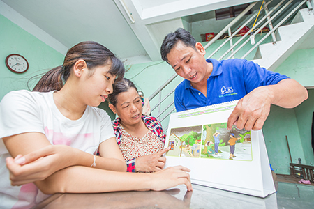Thuong explains flood evacuation procedures to Dinh Thi Xuan and daughter Thao, who have stopped by the local community center to seek the support group's advice.