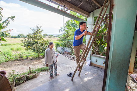 A local support group representative, Thuong, makes one of his regular house visits to ensure Phuoc's new roof is standing to up the increasingly severe climate change-related storms and natural hazards that pound central Vietnam.