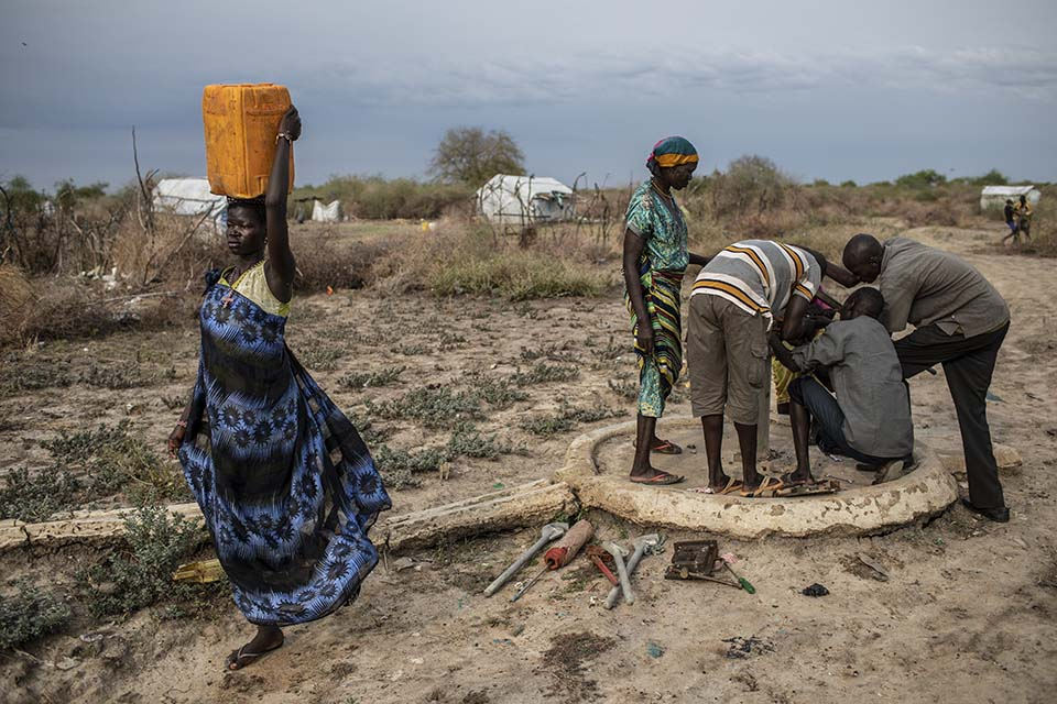 woman carrying jerry can walking past well pump mechanics at work in South Sudan