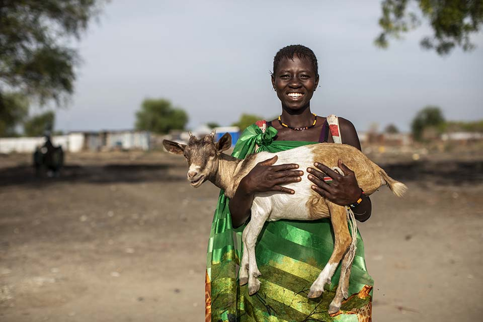 woman holds a goat at a livestock fair in South Sudan