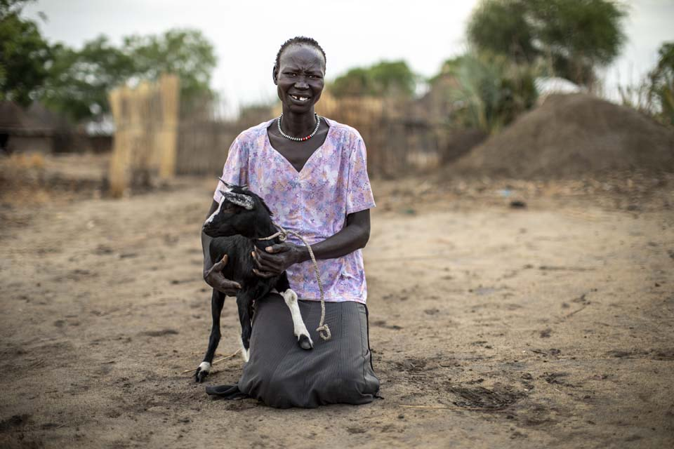 woman holds goat in South Sudan