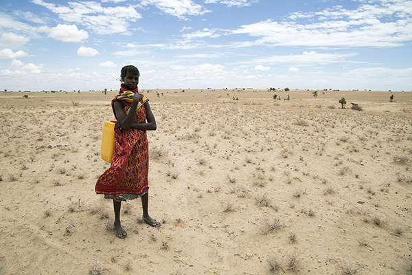 Woman stands in parched Kenya landscape