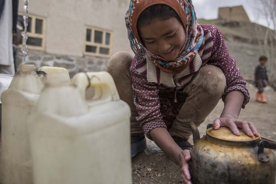 young woman collects water in Afghanistan