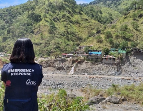 CRS emergency response team member viewing destruction of village due to flooding.