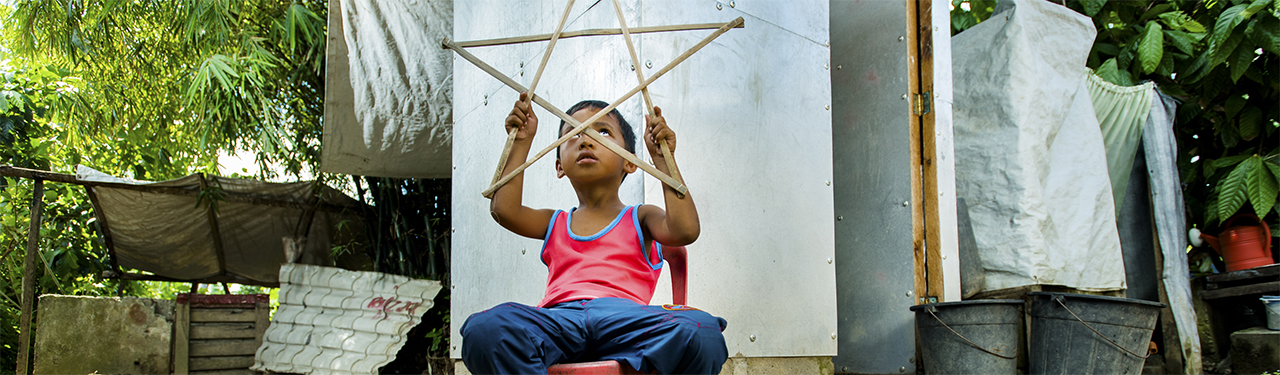 Ryle Andre Dalde plays with his Christmas star lantern in Palo Philippines.  Photo by Charlie David Martinez for CRS