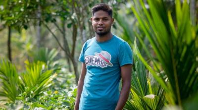 Man from Bangladesh stands among plants