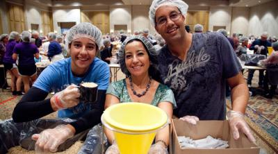 Volunteers at a Helping Hands event in Orlando pack food bound for Burkina Faso.
