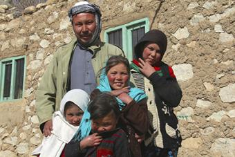 "Mahram Ali, with four of his eight children, is a farmer in Afghanistan's Central Highlands. He credits CRS with making his land more efficient. ""In the past this land was useless, and now I have production that provides my family income,"" he says. Photo"