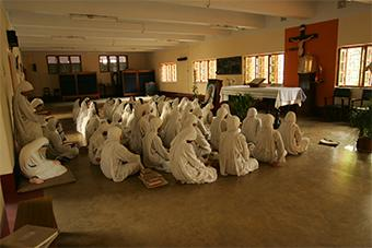 The Missionaries of Charity pray in their same chapel in 2006. Behind them, a statue of Mother Teresa sits in prayer with her sisters. Photo by Karl Grobl for CRS