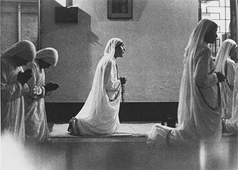 Mother Teresa is joined in prayer by her sisters, the Missionaries of Charity, in their chapel in Calcutta. Photo by CRS staff