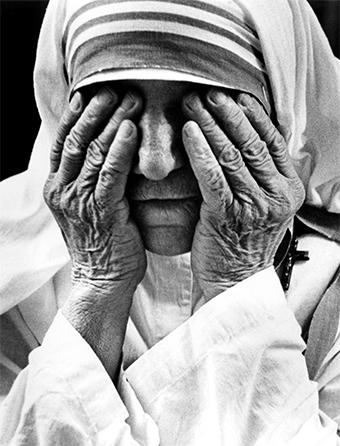 Mother Teresa takes a moment to shield her eyes with the hands she has used to hold so many people in need. Photo by Kent Kobersteen/CRS