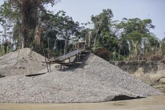 """Miners call this """"the beach."""" Located on the river's edge, it is the leftover rocks, gravel and sand from the gold mining process. Photo by Oscar Leiva/Silverlight for CRS"""