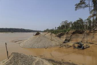 Using motors, sediment is dredged from the river and runs through a series of pipes and onto a platform with carpet where gold is trapped. Photo by Oscar Leiva/Silverlight for CRS